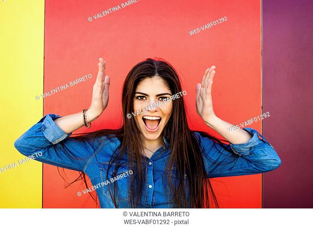 Portrait of screaming young woman in front of colourful wall