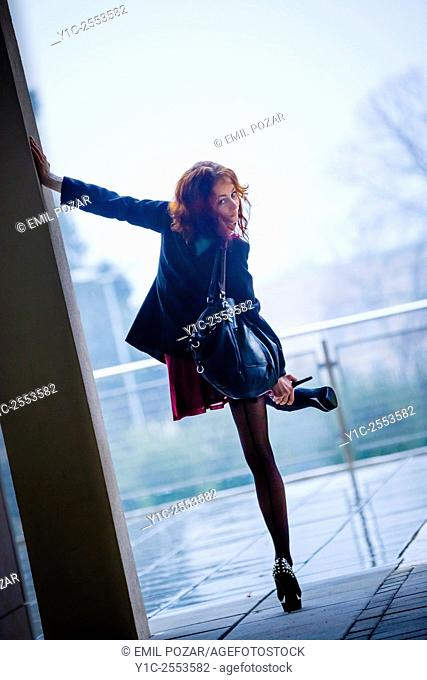 Young woman sexy on rainy day balancing on one leg