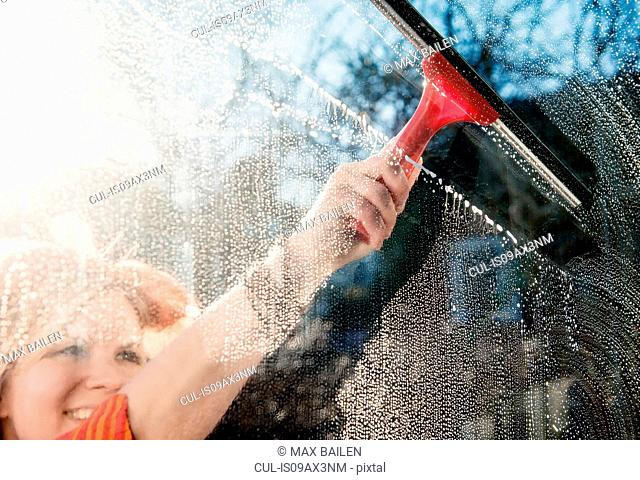 Woman outdoors cleaning sunlit window with squeegee