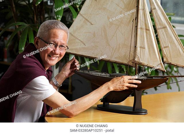 older man with model sail boat