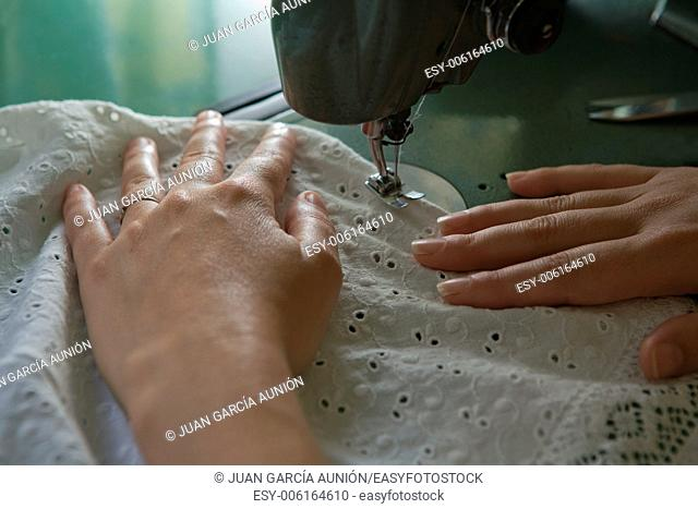 Hands of a dressmaker supporting a cloth while sewing on a sewing machine, Spain