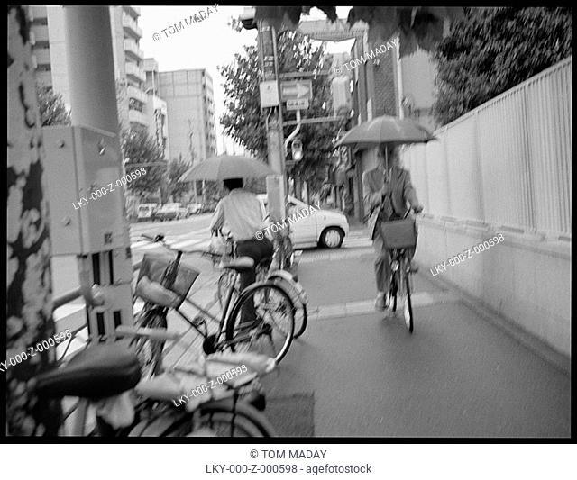 Men on bikes ride on sidewalk