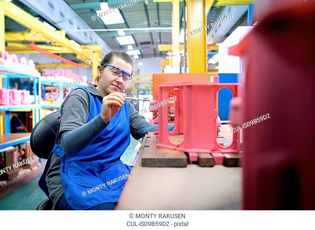 Female worker finishing wax component in precision casting factory
