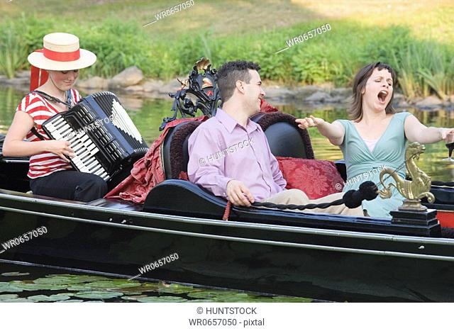 Mid adult man looking at a mid adult woman singing in a gondola