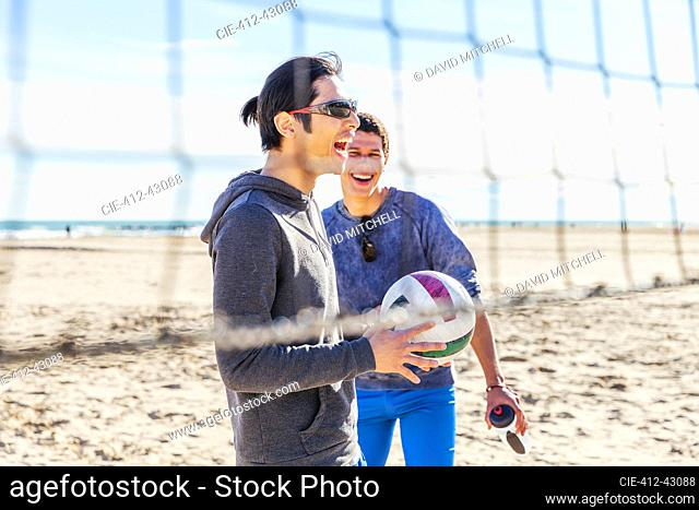 Happy male friends playing beach volleyball on sunny beach