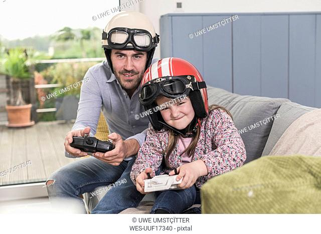 Young man and little girl wearing biker helmets, playing racing game with gaming consoles