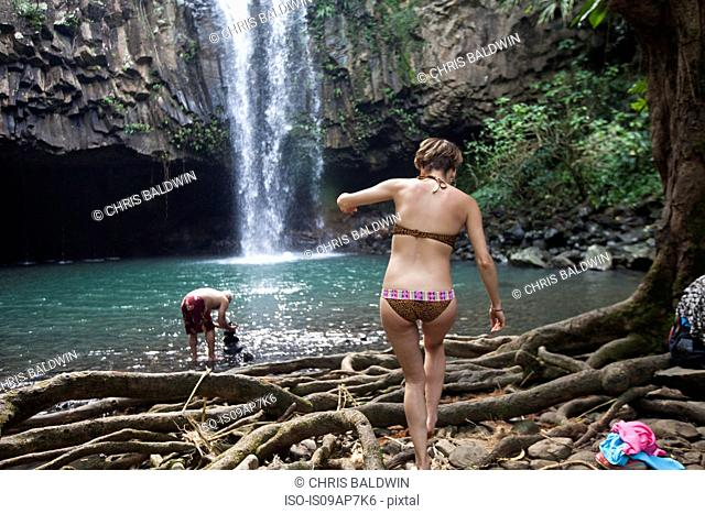 People swimming by waterfall