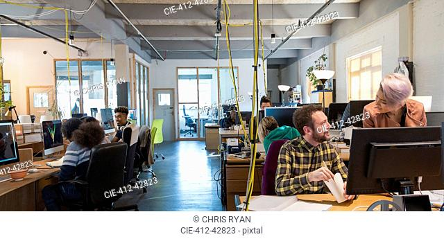 Creative business people working in open plan office