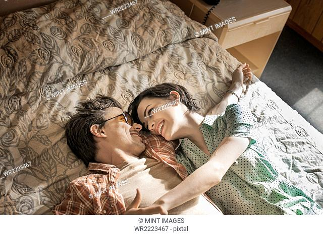 A young couple lying side by side on top of the bed in a motel room