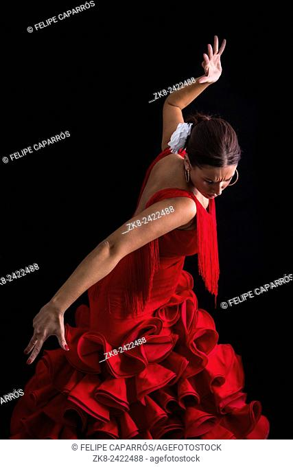 Flamenco dancer dressed in red with an expression of feeling passionate in black background