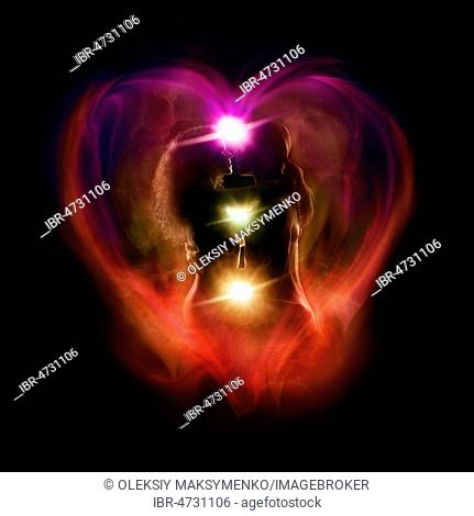 Tantra and Tantric sexuality spiritual concept of a couple making love with the colorful chakra energy flow glowing emanations in a shape of a heart around...