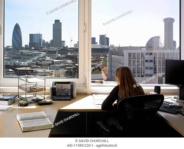 Office life and interiors (model released). Female employee sitting with back turned looking through book