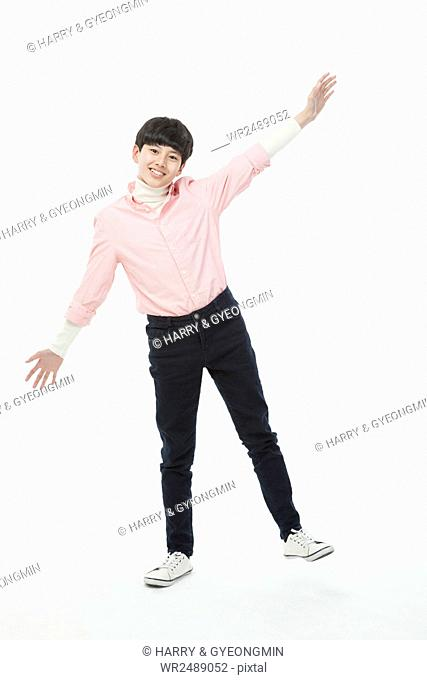 Smiling teenager boy in retro style casual standing on one foot opening his arms