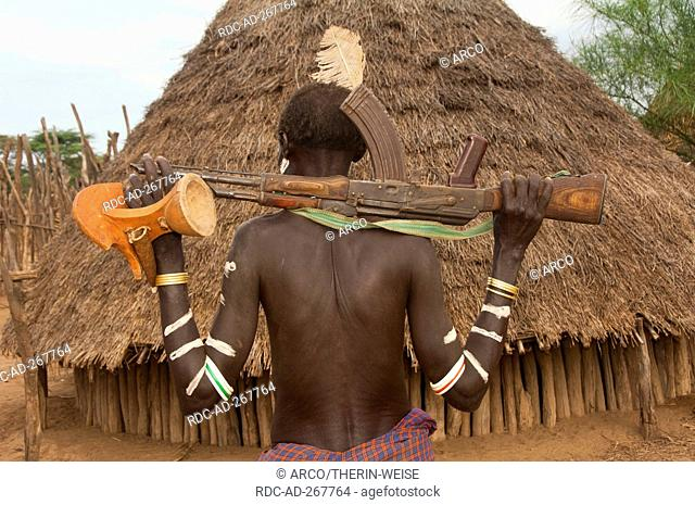 Karo warrior a gun and headrest on shoulder, Omo river valley, Southern Ethiopia