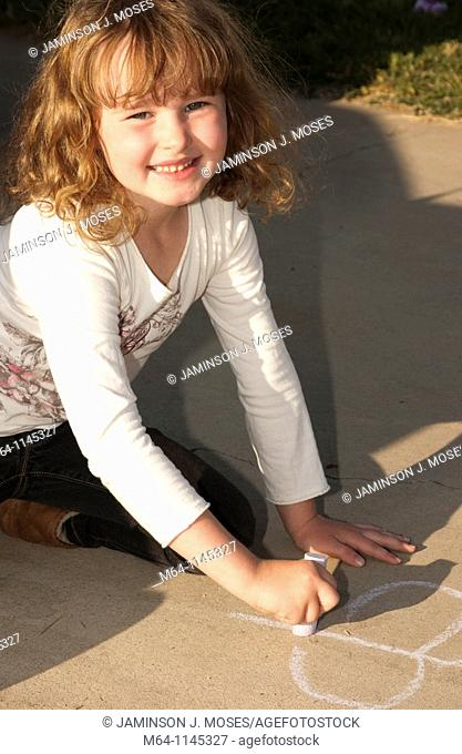 Young girl drawing on the sidewalk with chalk