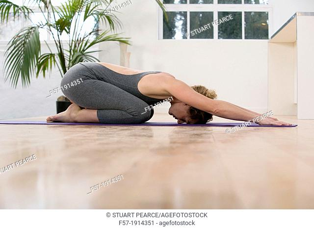 Healthy young woman doing the child's pose yoga position