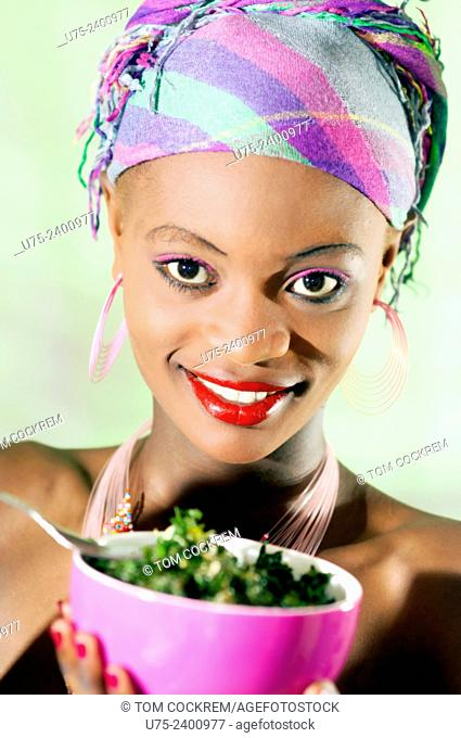 Young kenyan woman eating Sukuma Wiki, a traditional Kenyan vegetable stew made mostly from kale, in studio setting
