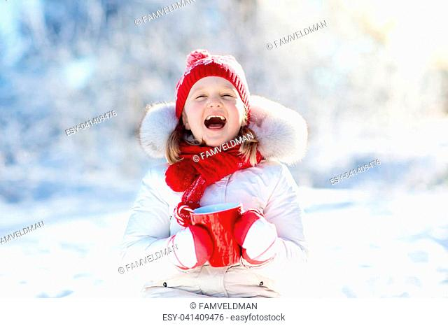 Child drinking hot chocolate with marshmallows in snowy winter park. Kid with cup of warm cocoa drink on Christmas vacation