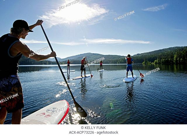 A group of paddle boarders make their way across the waters of Heffley Lake, North of Kamloops in the Thompson Okanagan region of British Columbia, Canada