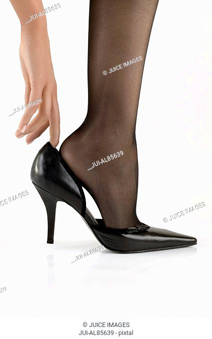 Studio shot of woman putting on high heels
