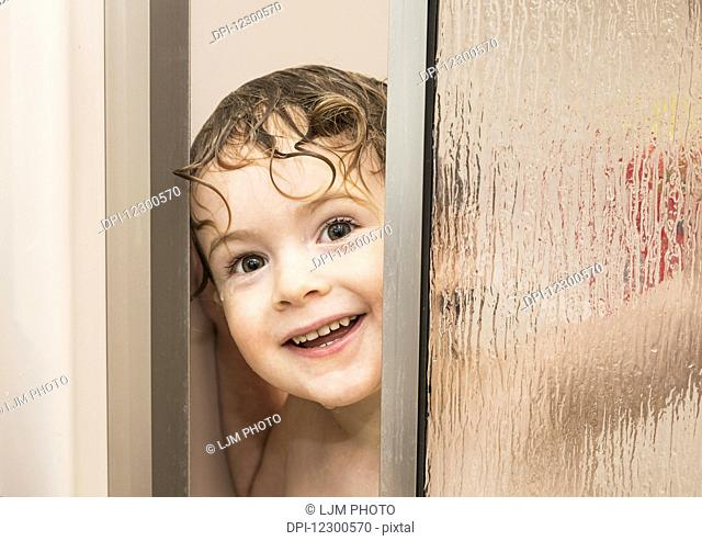 Youngster smiling and peeking out from behind a glass shower door in a bathroom; St. Albert, Alberta, Canada