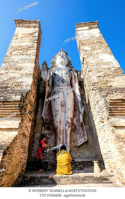 Asia. Thailand, old capital of Siam. Sukhothai archaeological Park, classified UNESCO World Heritage. Wat Mahatat. Women giving offerings to the Buddha
