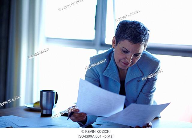Mature businesswoman reading paperwork in office
