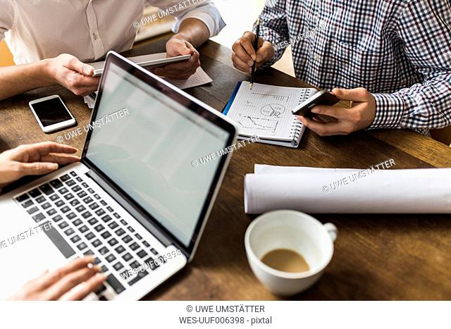 Colleagues at desk with smartphone, laptop and notepad