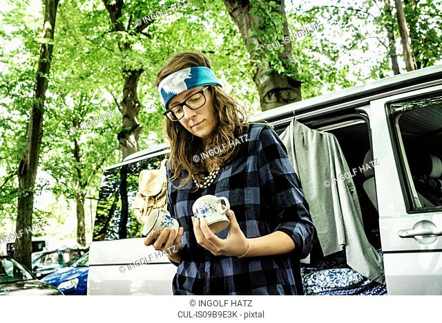 Female stall holder looking at second hand cups on stall at forest flea market