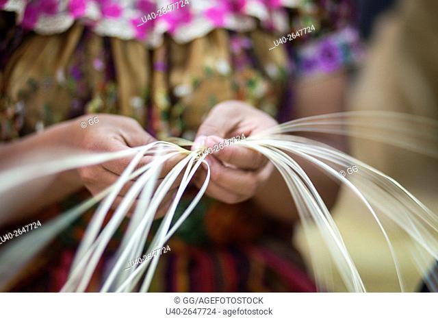 Guatemala, Quetzaltenango, close up of weavers hands making straw mat