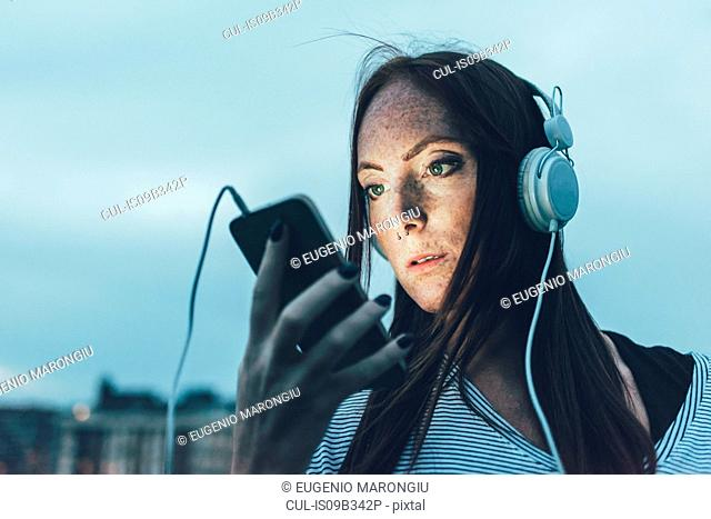 Young freckled woman listening to headphones looking at smartphone at dusk