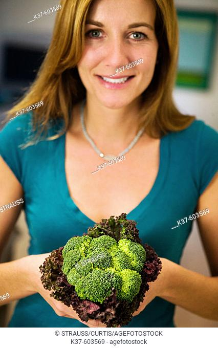 Caucasian mother holding bouquet of vegetables including broccolli