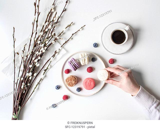 A hand taking macarons from a plate (seen from above)