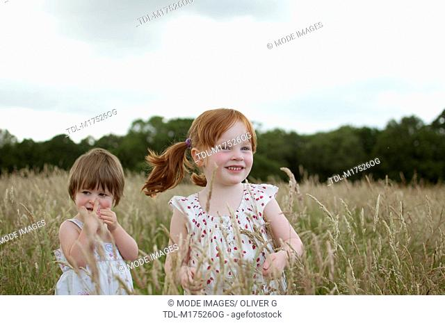 Two little girls playing in a field