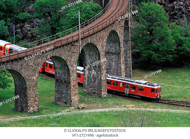 The Bernina Express passing under the viaduct in Brusio, Val Poschiavo, Switzerland Europe