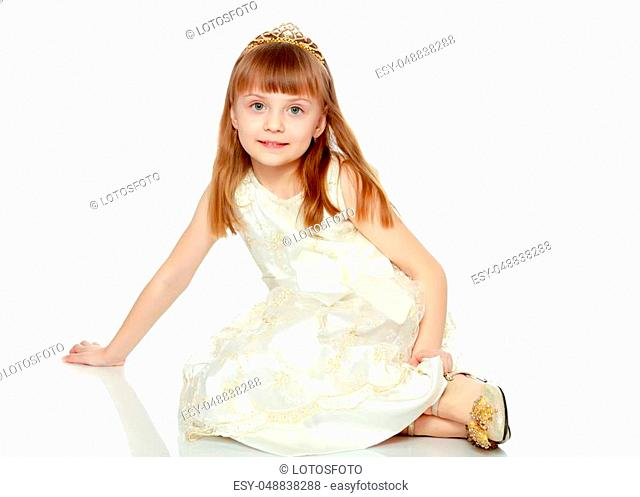 Beautiful little blonde girl with long blond hair and a short bangs. In a white ball dress.The girl sat down on the floor
