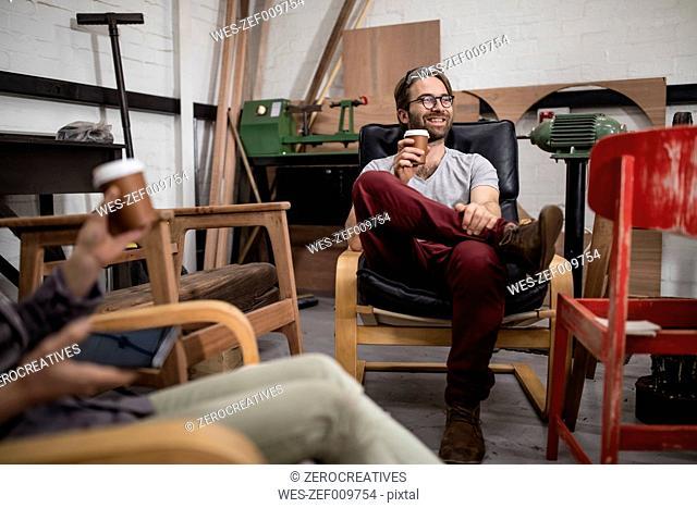 Man drinking coffee in workshop