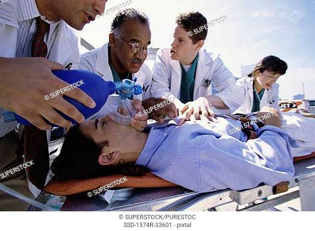 Group of doctors resuscitating a man lying on a stretcher