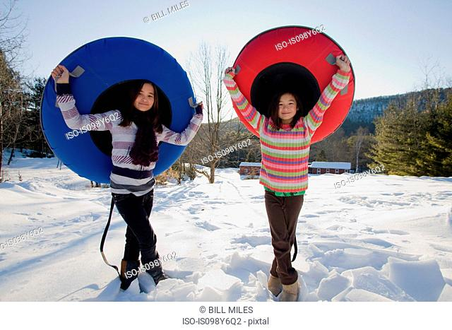Two girls with snow tubes