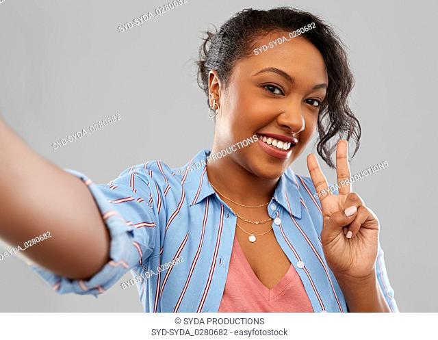 happy african american woman taking selfie