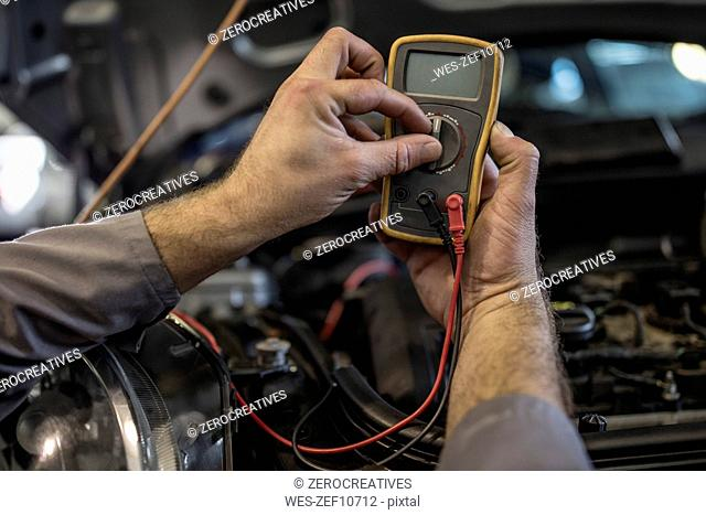 Close-up of car mechanic in a workshop using diagnostic equipment
