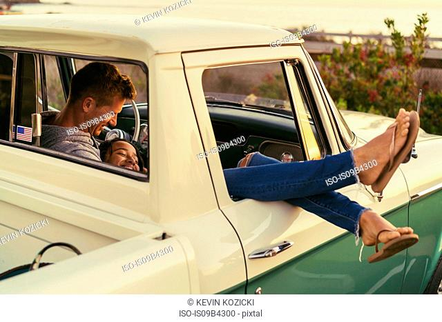 Romantic couple in pickup truck with legs out of window at Newport Beach, California, USA
