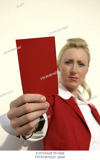 A woman wearing a red coat holds a red card in front of the camera