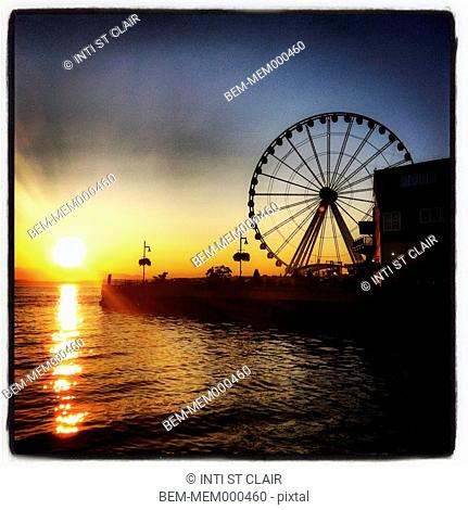 Silhouette of Ferris wheel on boardwalk at sunset, Seattle, Washington, United States