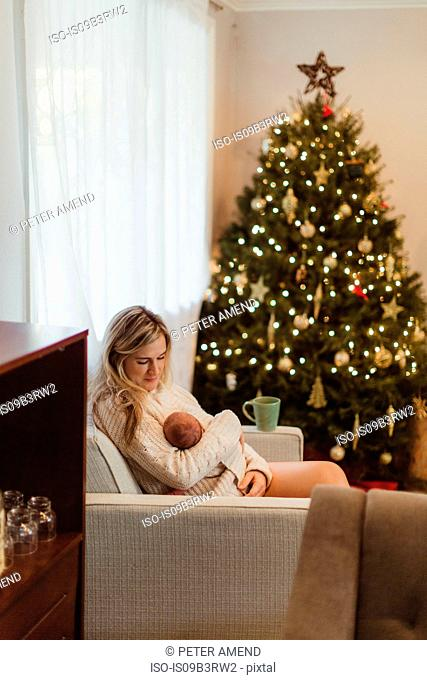 Mid adult woman sitting on sofa cradling new born baby daughter wrapped in cardigan at Christmas