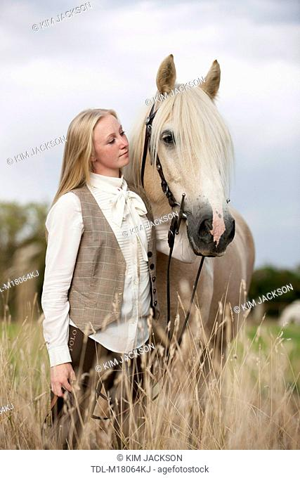 A young woman holding a palomino horse