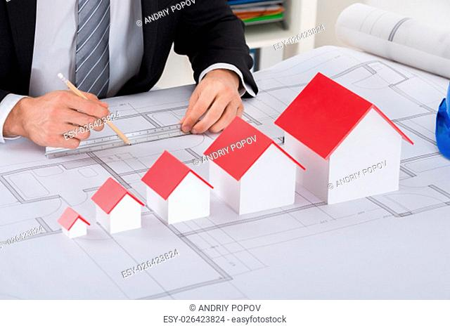 Close-up Of Male Architect Hand With House Models Working On Blueprint In Office