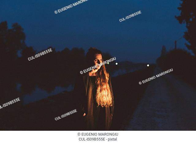 Young woman on roadside at night