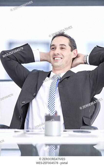 Smiling businessman sitting in office, hands behind head