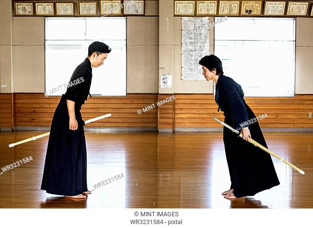 Female and male Japanese Kendo fighters standing opposite each other on wooden floor, bowing and greeting